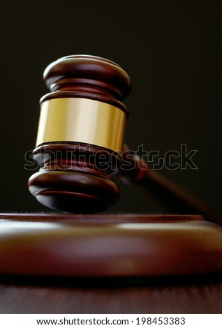 Close up low angle view of a wooden gavel with a brass band resting on its base, conceptual of a judge or auctioneer