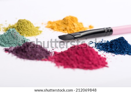 Close-up low angle view of professional make-up brush surrounded by heaps crashed in small pieces eye shadow in pink, blue, yellow, green and purple colours isolated on white background