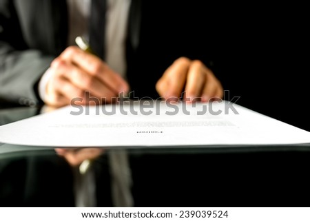 Close up low angle view of the blurred hands of a businessman signing a document or contract with focus to the text Contract. Shallow dof. - stock photo