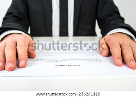Close up low angle view of the hands of a businessman reading a document or contract resting on either side of the page with focus to the text Terms and Conditions. - stock photo
