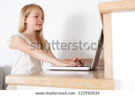 Close up low view side portrait of a young girl child using a laptop computer while sitting down on her home's wooden stairs, smiling. - stock photo