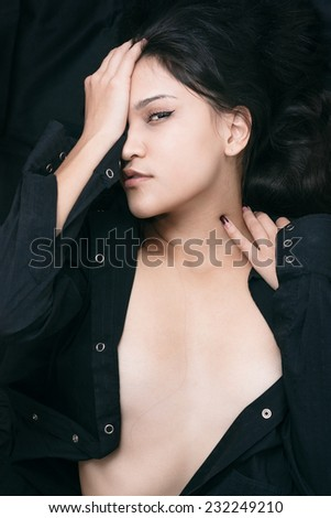 Close up Lying Seductive Young Woman in Unbuttoned Black Shirt, Showing her Cleavage While Covering One Eye and Looking at the Camera. - stock photo