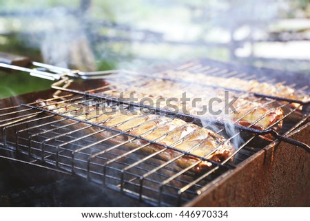 Close up mackerel, cooked on the grill in the open air flow. Five fishes on the grill in the smoke, tasty and fresh food, picnic, party, outdoor recreation. Grilled fish dish. - stock photo