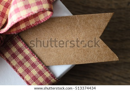 Close up (macro) of a blank brown gift tag on a white gift box with gingham ribbon tied to a bow.  Oak wood table surface below in soft focus.