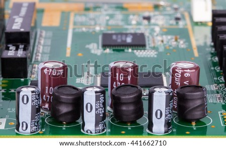 Close up / macro of a printed circuit board with electronic components: capacitors and coils - stock photo