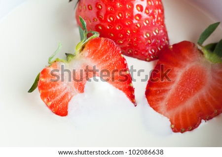 Close up (macro) of whole and halved fresh strawberries with leaves, partly immersed in double cream.