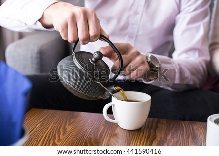 Close up macro photo of hands with tea cup. Man pours tea into a cup from a teapot.