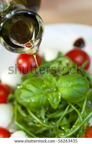 Close up macro photograph of olive oil dressing being poured onto a fresh rocket and basil salad with cherry tomatoes and balsamic vinegar - stock photo