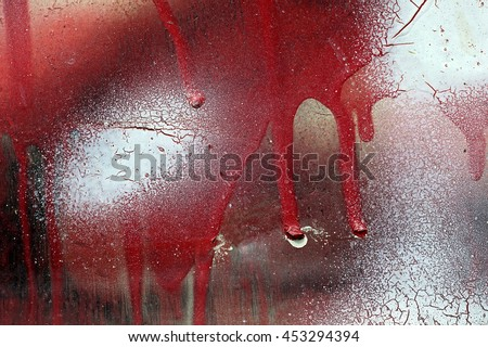 Close up,macro photography of cracked,scratched white and dripping red paint on grunge rough surface.Small part of dirty colored metal fence.Abstract textured background with space for copy text.