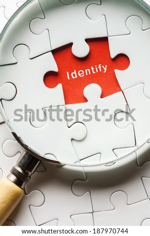 """Close up Magnifying glass searching missing puzzle peace """"identity"""" - stock photo"""