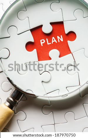 """Close up Magnifying glass searching missing puzzle peace """"plan"""" - stock photo"""