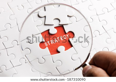 "Close up Magnifying glass searching missing puzzle peace ""STRATEGY"" - stock photo"