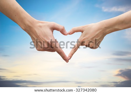 close up male and female hands making heart on blurred bright sunny sky backgrounds . passion in love concept,soft focused.picture for work about decorate,design,religious,valentines,wedding and etc. - stock photo