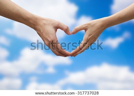 close up male and female hands making heart shape on blurred blur sky and clouds background.passion in love concept ,soft focused.healthcare and healthy life concept.happy family concept. - stock photo