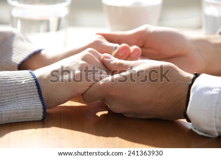 Close up male and female holding hands over table - stock photo