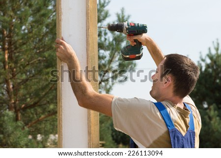 Close up Male Construction Worker Drilling on Wooden Plank During Building a House. - stock photo