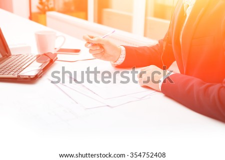 Close up male hands businessman. Closeup table and document. Businessman working at sunset with documents. Business man using laptop on table in with a cup of coffee. Background image. - stock photo