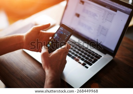Close up male hands holding big smart phone while connecting to wireless, businessman using technology sitting at modern loft wooden desk, people and modern devices everywhere, flare sun light - stock photo