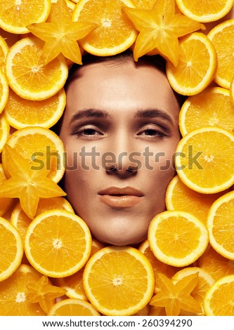 Close up male model face with make up in the middle sliced oranges - stock photo