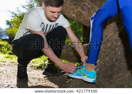 Close up Male Runner Ties A Female's Runner Shoelaces After Exercises In The Forest