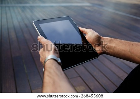 Close up male student hands using touch pad against wooden background, businessman working on his digital tablet with big copy space, hipster man's hands browsing with touchscreen device, filter - stock photo
