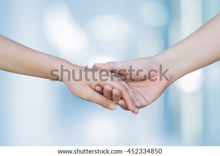 close up man and woman hand touching holding together on blurred background:love concept:healthcare:family and friends concept.hand of power family.lover hand shake on blur light blue background. - stock photo