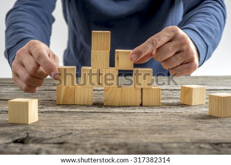 Close up Man Assembling a Tower Using Wooden Cubes on Top of a Rustic Table. - stock photo