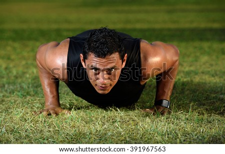 close up man doing push up on green grass