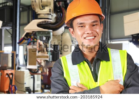Close up man factory engineer or worker with robot machine inside modern industrial manufacturing, automobile industry - stock photo