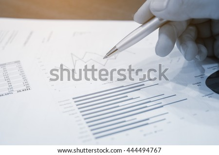 close up man hand finger with pen try to signing on paper application:businessman consider realize estimate quality value of work concept:statistic graph report of the year:vintage color effect filter