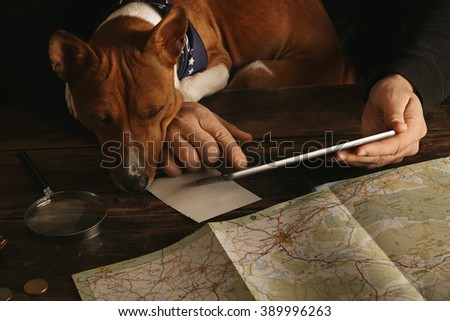 Close up man hands hold tablet  slide finger plan adventure route on aged wooden table with coins road map, magnifyer leather wallet Curious basenji dog sleeps on knees with head on table Side view