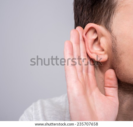 Close-up man holds his hand to his ear on the gray background. - stock photo