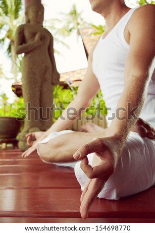 Close up man in hatha-yoga meditation in lotus asana - stock photo