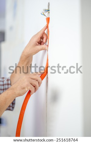 Close up Man Installing Orange Flexible Corrugated Cable Duct Inside the Building. - stock photo