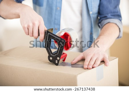 Close-up. Man packing boxes. Moving, purchase of new habitation. - stock photo