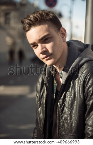 Close-up man portrait outdoor on street in city with blur background of town and buildings
