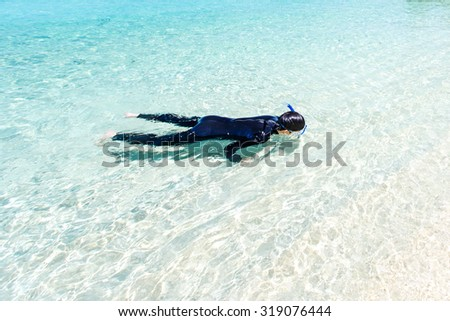 Close-up man snorkeling in crystal clear turquoise water at tropical beach, Koh Lipe, Thailand - stock photo