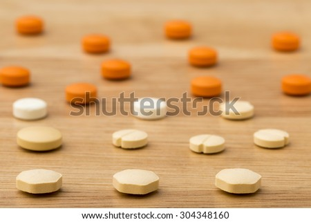 Close up medical pills on wooden table background - stock photo