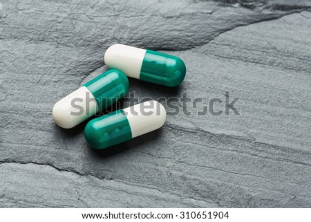 Close up medicine capsule or tablet black color stone, medical and health care concept - stock photo