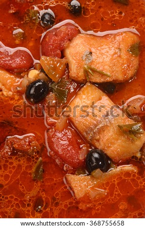 close up mediterranean fish soup with tomato and black olives - stock photo