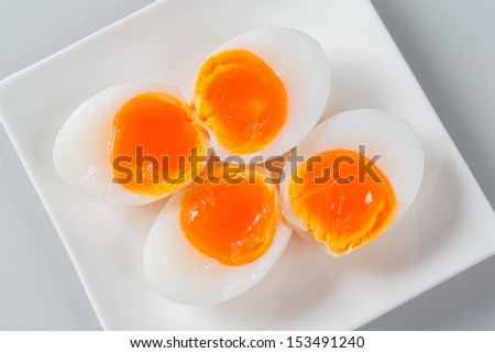 Close up medium soft boiled duck egg portion on white dish - stock photo