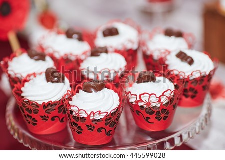 close-up meringue cakes decorated with chocolate hearts on wedding dessert table in restaurant - stock photo