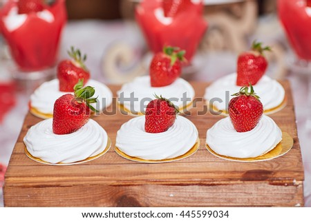 close-up meringue cakes decorated with fresh strawberry on wedding dessert table in restaurant - stock photo