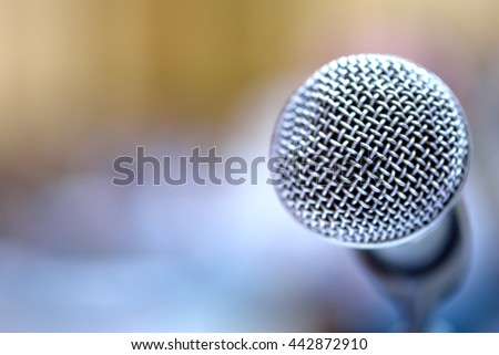 Close-up microphone in the conference room, soft focus.