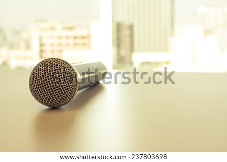 close up microphone on wooden table background - stock photo