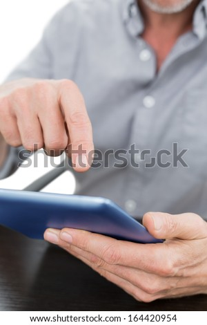 Close-up mid section of a businessman using digital tablet at table against white background