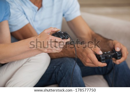 Close-up mid section of a couple playing video games in the living room at home - stock photo