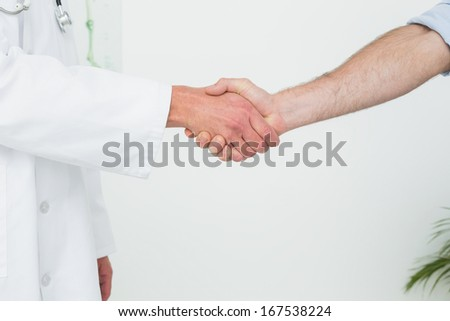 Close-up mid section of a doctor and patient shaking hands in the medical office
