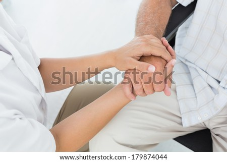 Close-up mid section of a doctor holding patients hand at medical office - stock photo