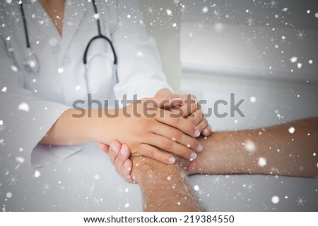 Close up mid section of a doctor holding patients hands against snow falling - stock photo